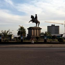 People pass by the statue of Menelik II and a crane undertaking reconstruction of the city in Addis Ababa, Ethiopia.